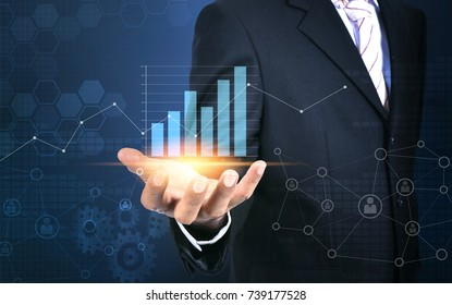 Businessman holding digital graph interface in his hand.