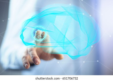 Businessman holding digital human brain with cells and neurons activity