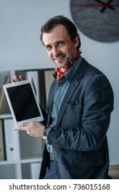 businessman holding digital tablet with blank screen and smiling at camera