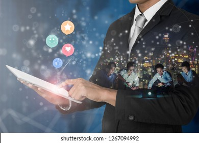 Businessman holding digital tablet with smiley face, like, love and star Emoticon on virtual touch screen, Customer service evaluation concept.