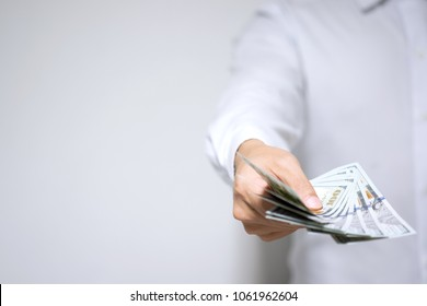 Businessman holding dollar money and giving money to you with copy space. Banker with money in hand displaying cash for customer loan, money transfer, investment and success concept. Selective focus.