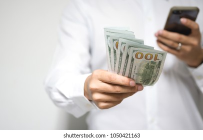 Businessman holding dollars money and smartphone in hand and giving money to you. Online banking and money transfer with mobile phone, e-commerce and investment concept. Selective focus, Copy space.