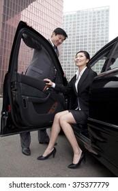 Businessman holding door open for businesswoman