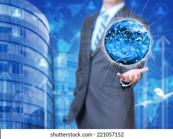 Businessman holding earth. Buildings as backdrop. Element of this image furnished by NASA