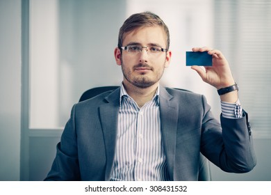 businessman holding empty business card in the office