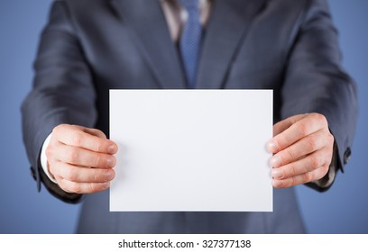 Businessman holding an empty sheet of paper, blue background