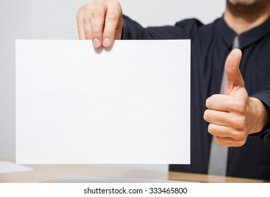 Businessman holding an empty sheet of paper and showing a thumb up sign, neutral background