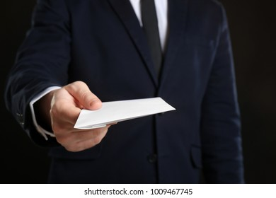 Businessman holding envelope with bribe on black background