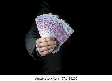 Businessman holding a fistful of 500 euro banknotes extended to the camera conceptual of wealth, success or payoff, cropped closeup over black background.