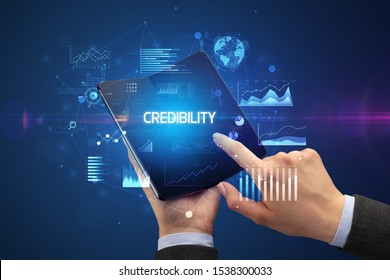 Businessman holding a foldable smartphone with CREDIBILITY inscription, successful business concept