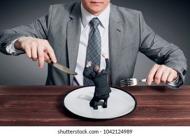 Businessman holding fork with knife and ready to eat small scared businessman on the plate. Hungry businessman ready to eating a competitor