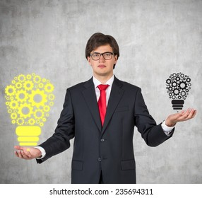 A businessman is holding gears in form of lightbulb