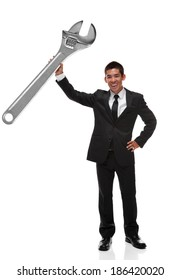 Businessman holding a giant adjustable wrench up business tool concept