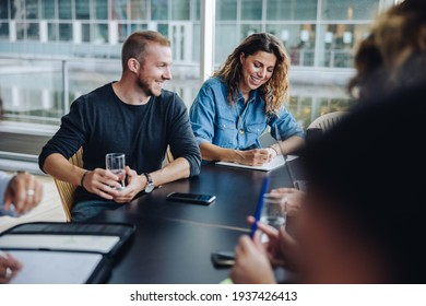 Businessman holding glass of water sitting in meeting room with colleagues around. Group of men and women having a meeting in office boardroom.