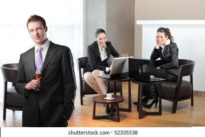Businessman holding a glass of wine and two smiling businesswomen on th background