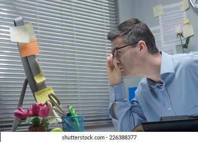 Businessman holding glasses and staring at computer close-up, vision problems concept.