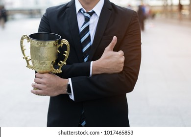 businessman, holding up a gold trophy cup is winner in a competition with city background. Win concept.