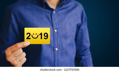 Businessman holding golden business card with number 2019 on blue background. Concept for success in the future goal and passing time. New Year 2019 greeting card