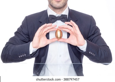 Businessman holding a golden egg for Easter