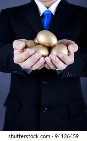 Businessman holding a golden eggs - investment concept