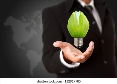 Businessman holding green light bulb, concept of saving energy