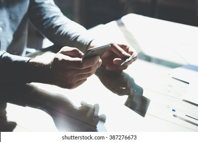 Businessman holding hand credit card and using smartphone. Online payments plastic card. Horizontal mockup. Blurred, film effect.