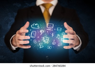 Businessman holding hand drawn media icons
