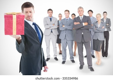 Businessman holding hand out in presentation against present