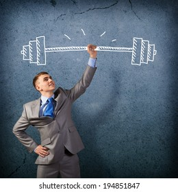 businessman holding a hand sketched barbell, concept achievements in business
