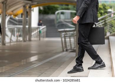 Businessman holding a handbag and walking downstairs