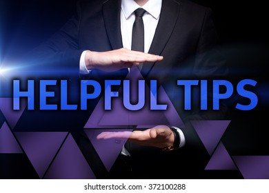 "Businessman holding in the hands a glowing blue text ""Helpful Tips"". Business concept. Internet concept"