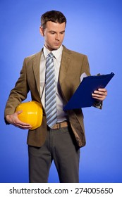 Businessman holding hardhat and looking at clipboard