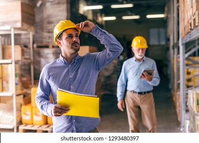 Businessman holding helmet and folder with documents while looking up and standing in warehouse. In background his colleague walking with tablet.