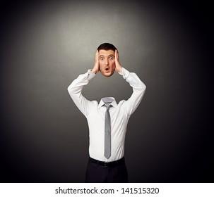 businessman holding his amazed head in hands. photo over dark background