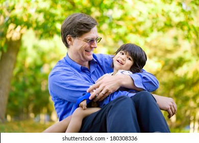 Businessman holding his disabled son on grass. Child has cerebral palsy.