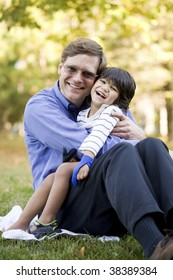 Businessman holding his disabled son on grass