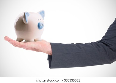 Businessman holding his hand out against piggy bank