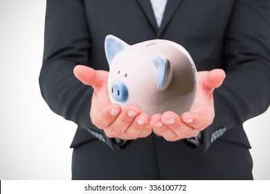 Businessman holding his hands out against piggy bank