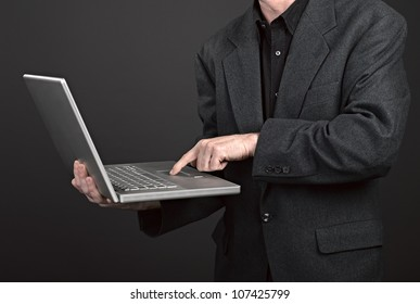 Businessman holding his laptop on black