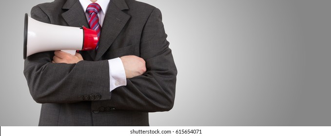 businessman holding his megaphone on grey background