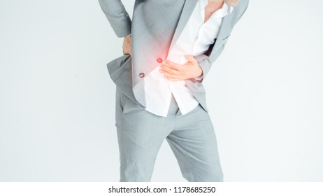 Businessman holding his stomach in pain with stomachache or indigestion.Man in office uniform having a stomachache / food poisoning / stomach problems.
