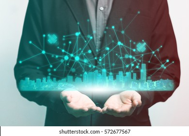 Businessman holding a hologram plan of city and communication through satellite. Worldwide connection technology interface.
