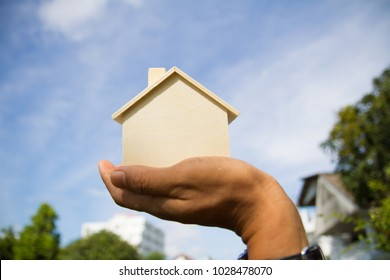 Businessman holding home model, house ownership or real estate business concept, loan conceptfor