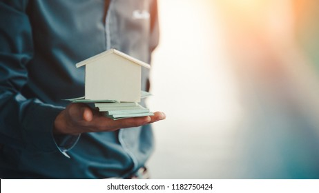Businessman holding home model. Loan concept