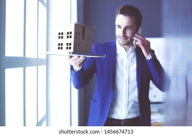 Businessman holding house miniature on hand standing in office.