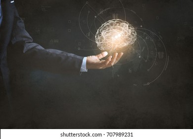 Businessman holding human brain and icon customer digital network with effective business mindset on paper texture background