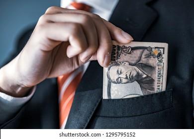 businessman holding Japanese yen bill