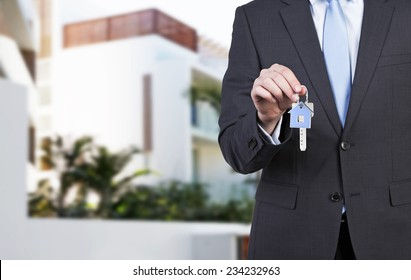 Businessman is holding a key as a metaphor of pure success.