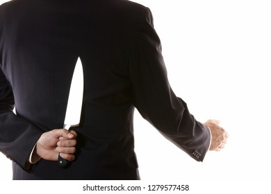 Businessman holding a knife behind his back is about to shake hands. This is to signify someone who is a traitor and not to be trusted about to stab you. Copy space.