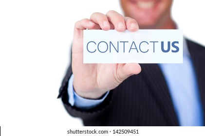 Businessman holding a label with contact us written on it on white background